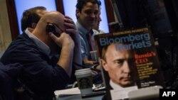 Трейдеры на Нью-Йоркской фондовой бирже. На столе - выпуск журнала Bloomberg Markets с Владимиром Путиным на обложке. 3 марта 2014 года.