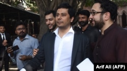 Pakistani journalist Cyril Almeida (center) arrives at the High Court to face treason charges in Lahore on October 8.