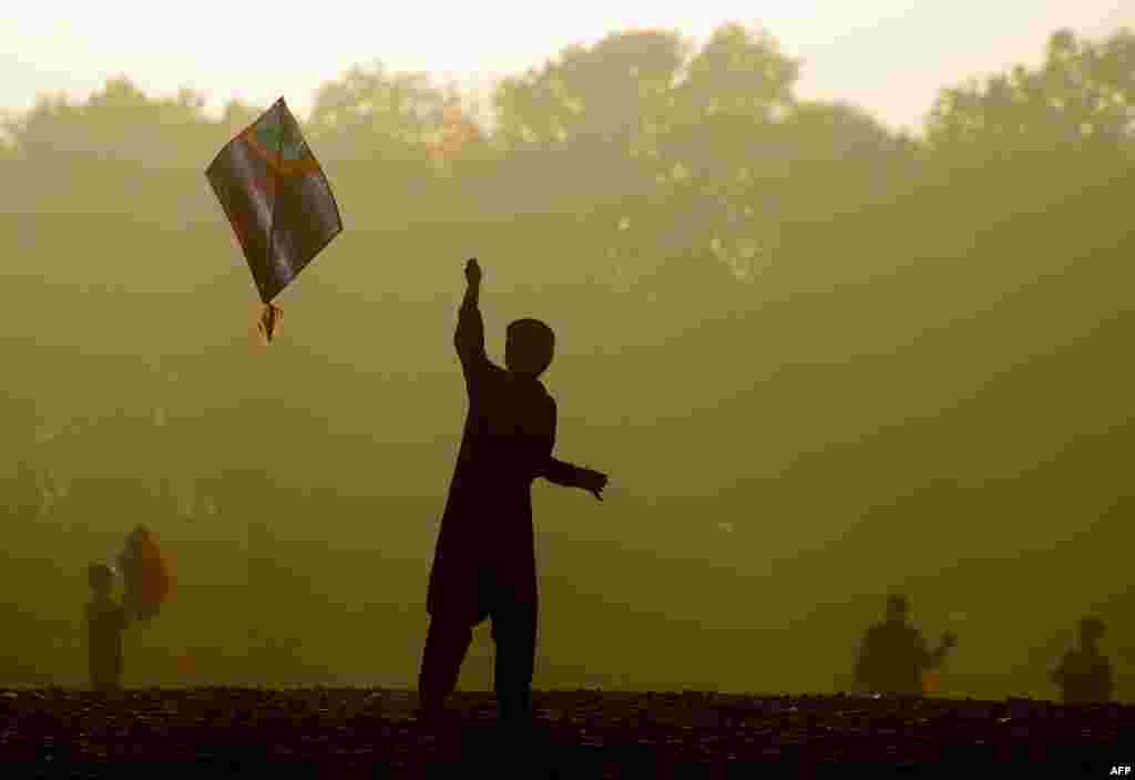 An Afghan child plays with a kite as sun sets on the outskirts of Herat. (AFP/Aref Karimi)