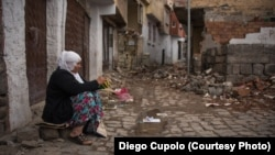 A woman knits in front of a home that was destroyed by a bomb during fighting in Sur.