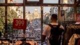 Praga. Dükanyň içinden demonstrasiýany synlap duran adam. 4-nji iýun, 2019.