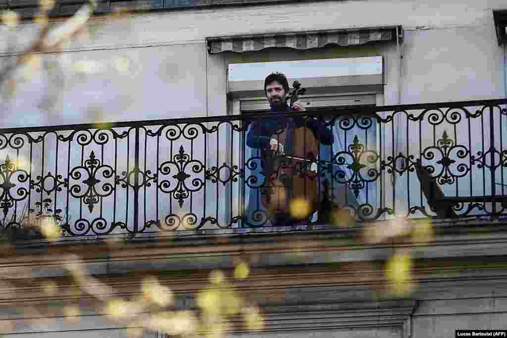 Віолончеліст Каміло Перальта грає на своєму балконі в Парижі під час карантину, спрямованого на стримування поширення COVID-19