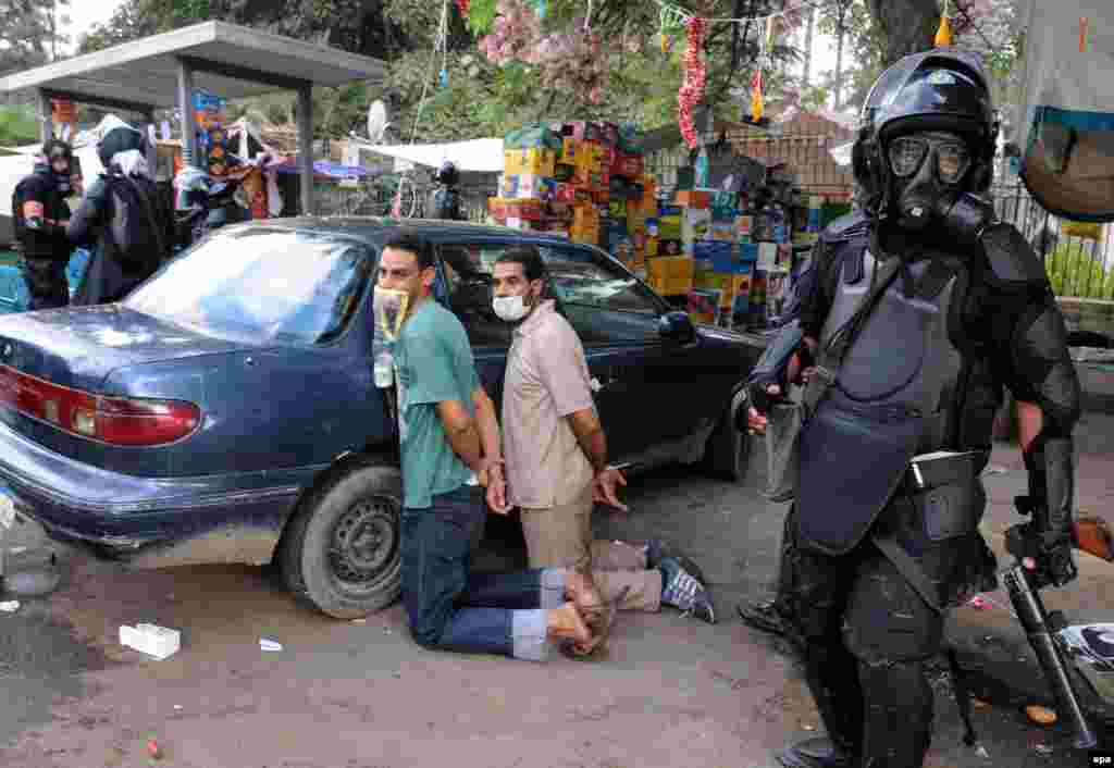 Egyptian security forces detain protesters at a protest camps on Nahda Square, near Cairo University.
