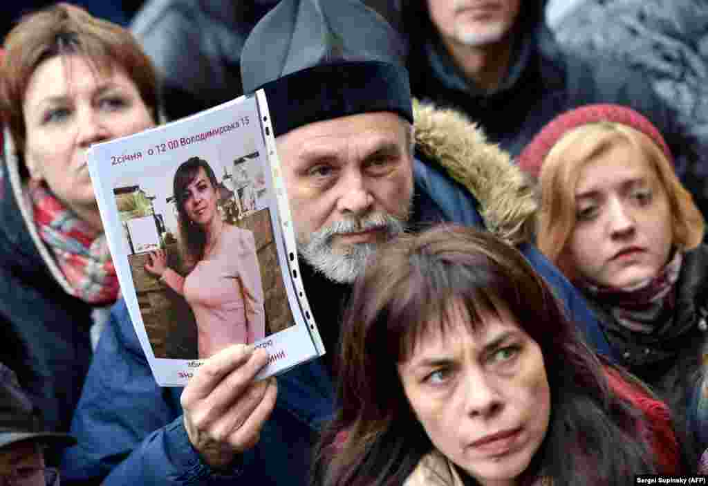 An Orthodox priest holds a picture showing slain Ukrainian lawyer Iryna Nozdrovska as he together with another few hundred activists rally outside the Kyiv police headquarters on January 2. (AFP/Serhey Supinskiy)