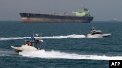 Iran -- Revolutionary Guards drive speedboats in front of an oil tanker during a ceremony to commemorate the 24th anniversary of the downing of Iran Air flight 655 by the US navy, at the port of Bandar Abbas, 02Jul2012