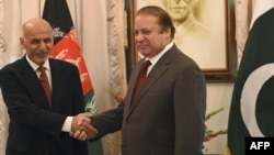 Afghan President Ashraf Ghani (L) and Pakistani Prime Minister Nawaz Sharif shake hands at the Prime Minister House in Islamabad on November 15, 2014.