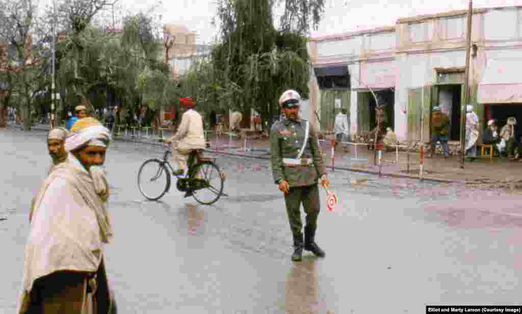 "A traffic policeman after a rainfall in Jalalabad. When Elliot last saw Afghanistan, in 2011, he felt that despite the change in the security situation the country was much the same. ""The way Afghans describe things is, 'new saddle, same donkey,'"" Elliot says."