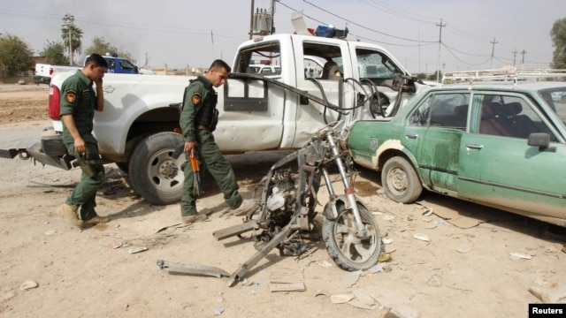 Iraqi security personnel inspect the site of a bomb attack in Kirkuk on October 24, where a child was killed.
