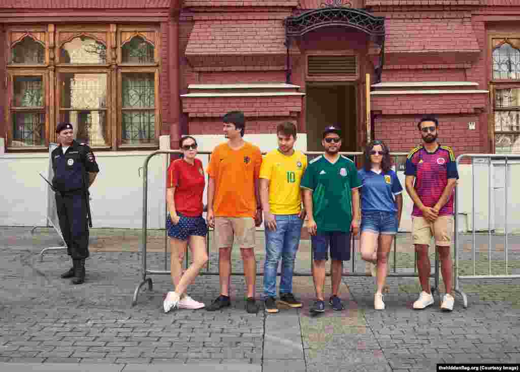 The activists near a Russian policeman. The officer may have been wondering what a Dutch fan is doing in Russia -- Holland failed to qualify for the 2018 World Cup.