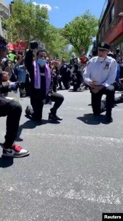 New York, polițist în genunchi, în semn de solidaritate cu protestatarii, 31 mai 2020.