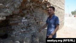 Житель Кызылорды Серикбай Сейдильдаев показывает на обрушившуюся часть стены в здании общежития, в котором проживает. Кызылорда, 4 августа 2015 года.