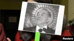 Гражданская активистка из Алматы стоит с черно-белым плакатом, на котором изображен президент Нурсултан Назарбаев.