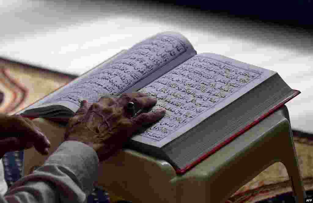 Мужчина читает Коран в одной из мечетей пакистанского города Карачи. 13 июля 2016