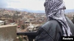 A member of the Free Syrian Army with an assault rifle stands guard during a patrol in the western Syrian border town of Zabadani on January 16.