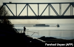An Afghan man watches a ship travel along the Amu-Darya River on the border between Afghanistan and Uzbekistan