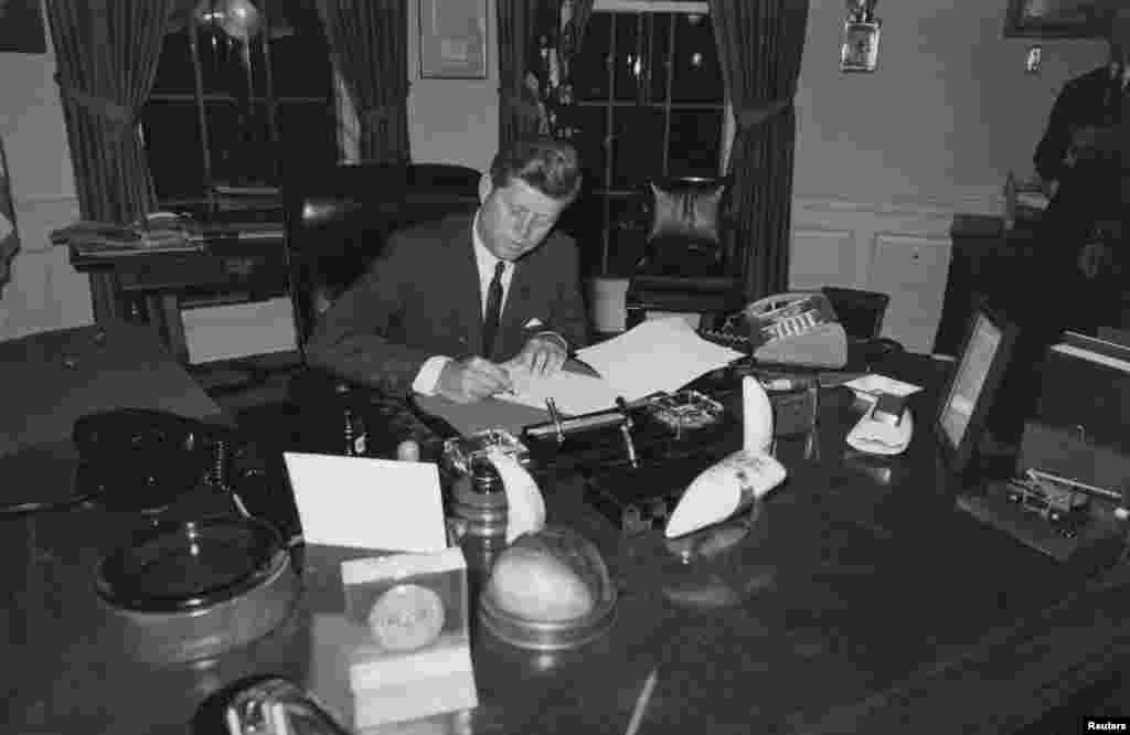 President Kennedy at the White House signing a proclamation to stop the delivery of offensive weapons to Cuba during the Cuban missile crisis in October 1962.