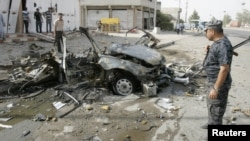 Iraqi security personnel inspect the site of a car-bomb attack in Kirkuk on August 16.