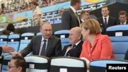 რუსეთის პრეზიდენტი ვლადიმირ პუტინი (მარცხნივ), ფიფას პრეზიდენტი ზეპ ბლატერი და გერმანიის კანცლერი ანგელა მერკელი.