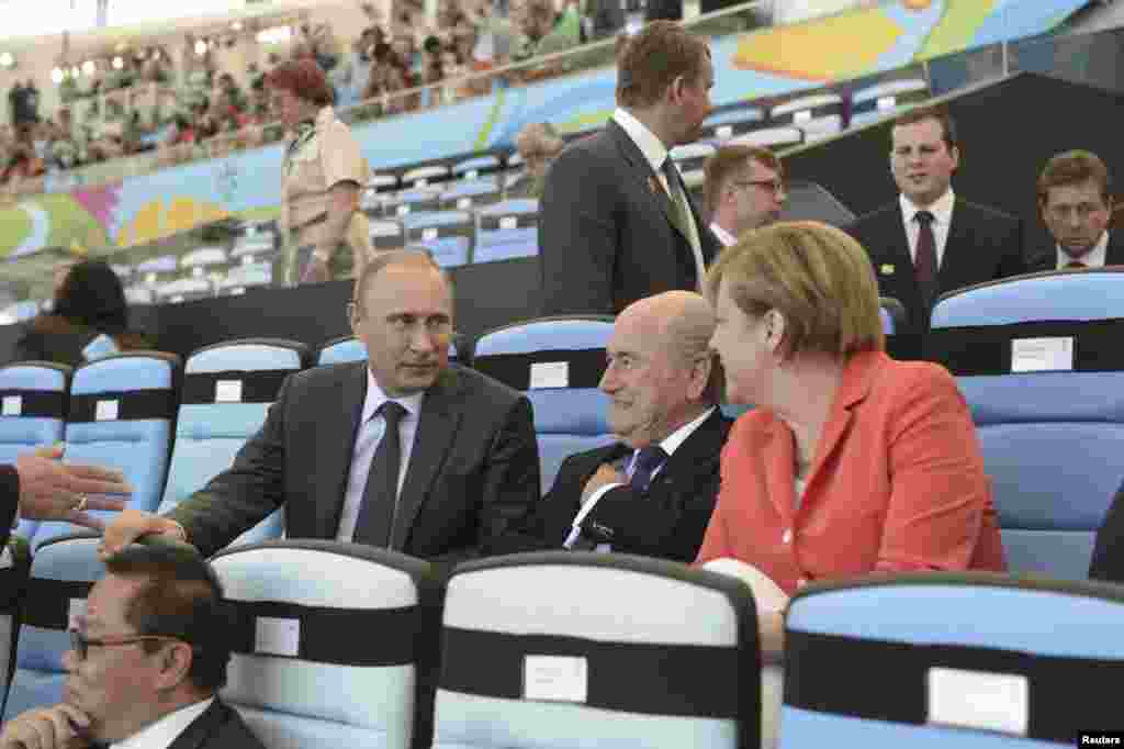 Russian President Vladimir Putin speaks to FIFA President Sepp Blatter and German Chancellor Angela Merkel during the 2014 World Cup final between Germany and Argentina at the Maracana stadium in Rio de Janeiro on July 13, 2014.