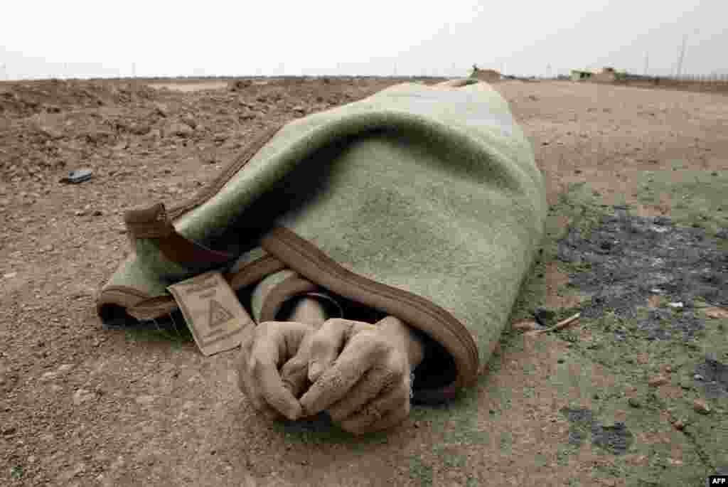 The body of an Iraqi soldier lies wrapped in a blanket following the British assault on the Al-Faw peninsula on March 22.