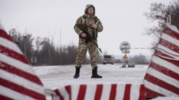 A Ukrainian guard stands ready at the border in Milove.