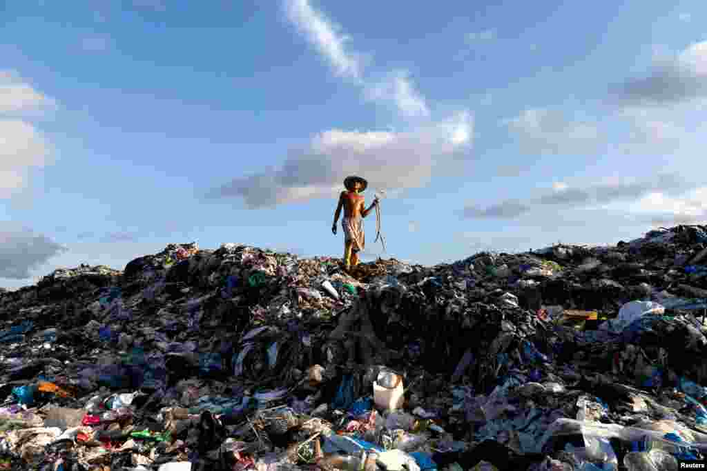 A man walks atop a huge landfill dump as he looks for firewood outside Yangon, Burma. (Reuters/Soe Zeya Tun)