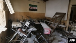 Syria -- A pre-Baath Syrian flag, now used by the Syrian opposition, hangs in a heavily damaged classroom after a barrel bomb hit a school in Syria's northern city of Aleppo Saif al-Dawla district, where control is split between the Syrian regime and opposition.