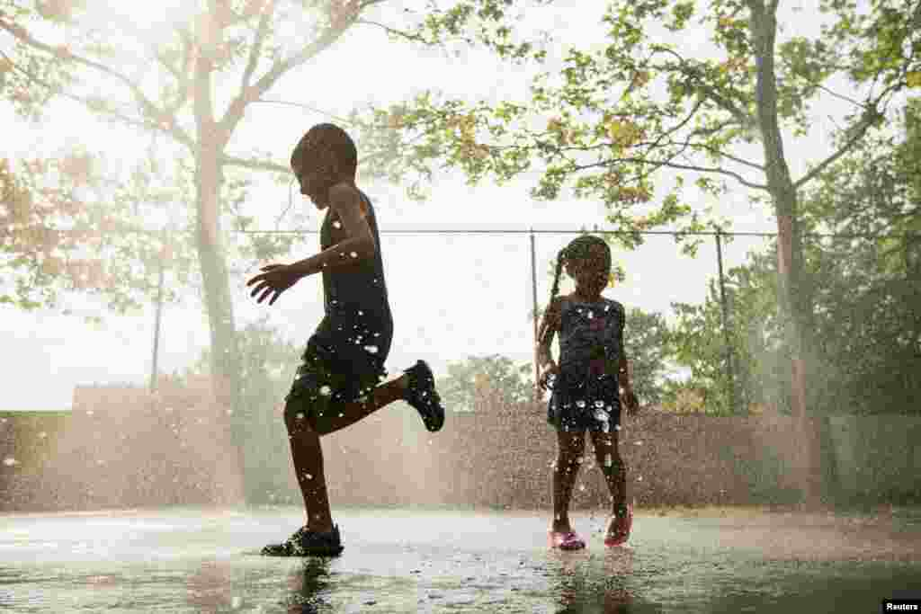 Children run through a sprinkler system installed inside a playground to cool off in the summer heat in New York City on July 17.