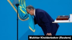 Qasym-Zhomart Toqaev kisses the state flag during his presidential inauguration ceremony in Nur-Sultan on June 12.