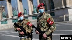 Hungarian military police officers patrol Budapest's deserted Heroes' Square during a coronavirus emergency.