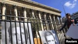 Фотографии на француските новинари Стефани Тапониер и Херв Шескуиер поставени пред старата берза во Париз.