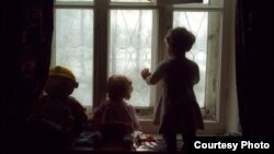 2002 елгы бу фотода Петербур янындагы Усть-Ижорада ВИЧ инфекцияле ятимнәр тупланган махсус балалар йортында әле аягына басып кына килүче кыз бала тәрәзә аша дөньяны күзәтә. Петербурда яшәүче фотограф Александр Беленький күп еллар буена Русиянең балалар йортларында балаларның тормышы турында фотолар төшереп килгән.