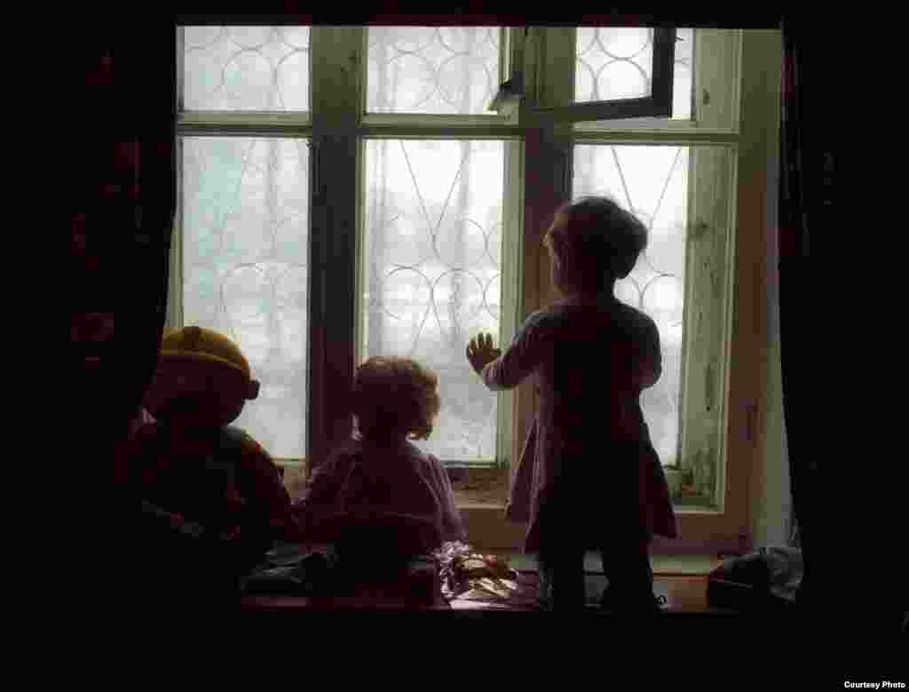 A toddler gazes out a window at a special orphanage for HIV-infected children in Ust-Izhora outside St. Petersburg, circa 2002. Children at this orphanage were typically abandoned by their parents. They received medical treatment but were virtually sealed off from outside life and were rarely allowed to leave the grounds of the facility.