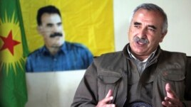 Acting PKK military commander Murat Karayilan in front of an image of rebel leader Abdullah Ocalan