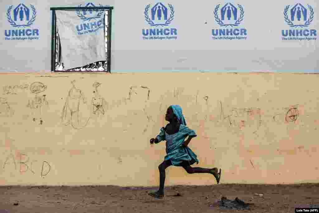 A young girl runs at the Malkohi refugee camp in Jimeta, Nigeria. (AFP/Luis Tato)