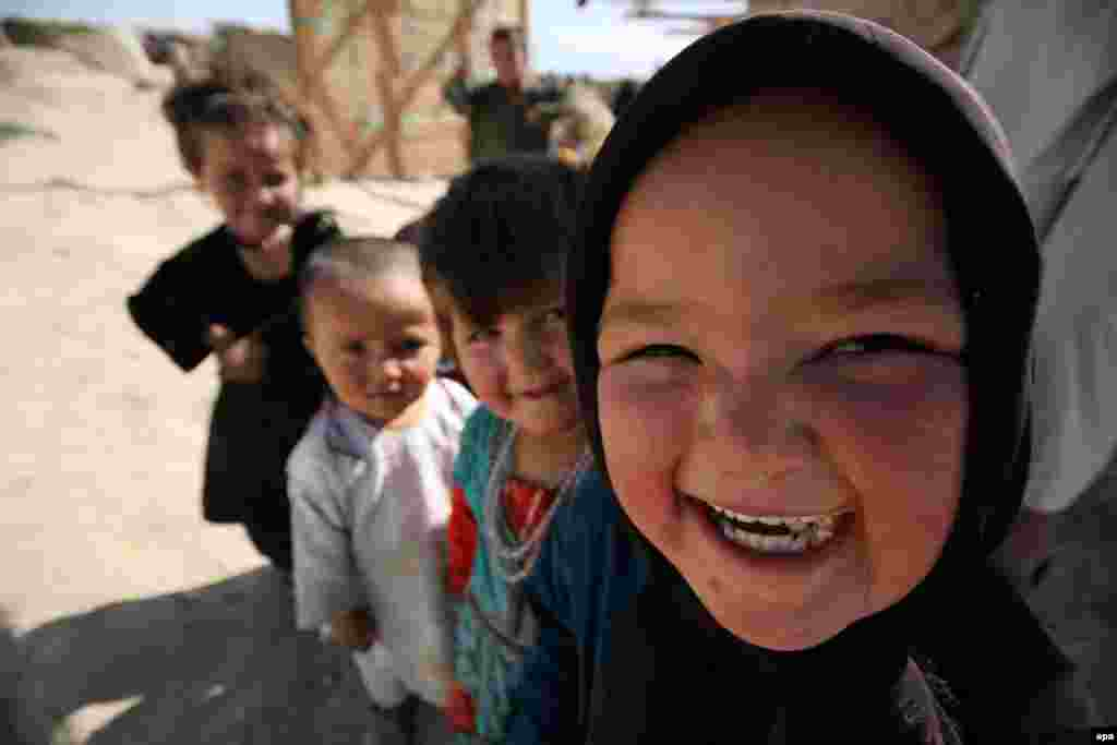 Afghan children pose for a photograph at a temporary shelter in Mazar-e Sharif. (epa/Sayed Mustafa)