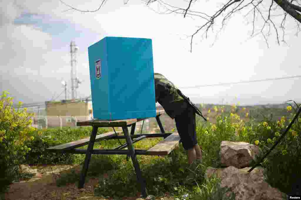 An Israeli soldier casts his ballot in parliamentary elections behind a mobile voting booth in the West Bank Jewish settlement of Migdalim, near Ariel. Millions of Israelis voted on March 17 in a tightly fought election, with Prime Minister Benjamin Netanyahu facing an uphill battle to defeat a strong campaign by the center-left opposition to deny him a fourth term in office. (Reuters/Amir Cohen)