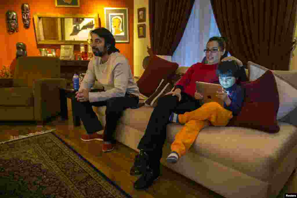 Naadiya Manzur (center), the director of the Treehouse Nursery and Kindergarten, watches television with her husband, Omar, and son, Zidaan, at their home in Islamabad.
