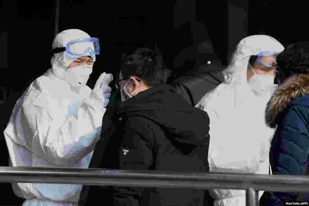 Люди в защитных комбинезонах проверяют пассажиров на станции метро в Пекине 24 января 2020 года