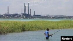 """Мужчина, пришедший порыбачить на озеро Балхаш. На заднем фоне - трубы медеплавильного завода, принадлежащего компании """"Казахмыс"""". Балхаш, 14 июня 2012 года."""