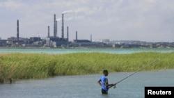 Житель города Балхаша рыбачит на озере. На дальнем плане - трубы медеплавильного завода.