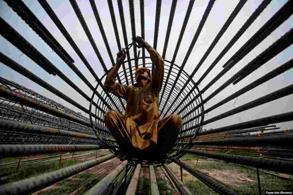 A worker ties steel bars at a construction site in Peshawar, Pakistan. (Reuters/Fayaz Aziz)