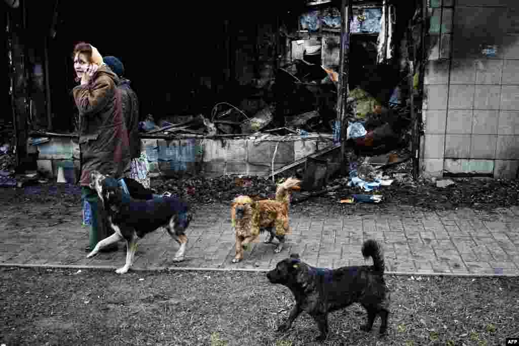 A pack of stray dogs follows women walking past a a burnt-out shop in the Kyivsky district of the eastern Ukrainian city of Donetsk. (AFP/Dimitar Dilkoff)