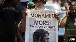 Человек держит портрет Мухаммеда Мурси во время демонстрации с требованием восстановления его в должности президента. Каир, 17 июля 2013 года.