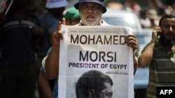 A man holds a portrait of ousted President Muhammad Morsi as thousands of his supporters demonstrate for his reinstatement close to the cabinet headquarters in Cairo on July 17.