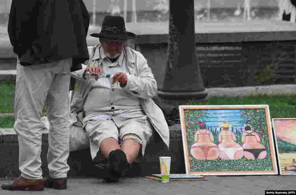 A street artist drinks vodka as he sells his paintings to tourists in the center of the Ukrainian capital, Kyiv. (AFP/Sergei Supinsky)