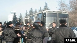 Police arresting demonstrators in Almaty and loading them on a bus