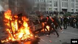 Участники протестов в Бишкеке жгут автомобиль у здания правительства. Протесты обернулись смещением действовавшего президента Кыргызстана Аскара Акаева. 24 марта 2005 года.