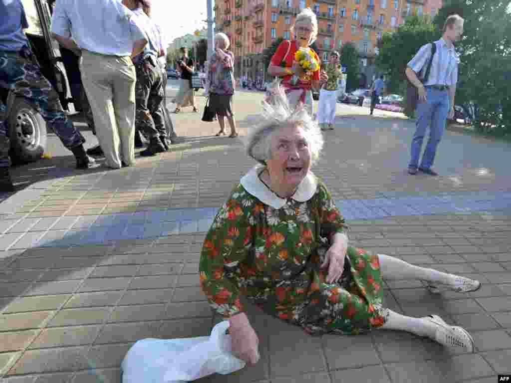 Стара жінка плаче серед представників міліції, які затримують активістів опозиції під час мітингу, присвяченого 20-й річниці проголошення суверенітету Білорусі. Мінськ, 27 липня. Photo by Victor Drachev for AFP