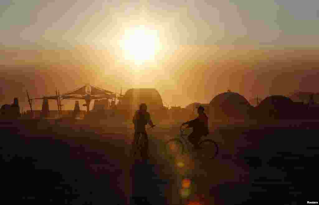 Participants bike across the desert at sunrise at the 2013 Burning Man arts and music festival in Nevada.